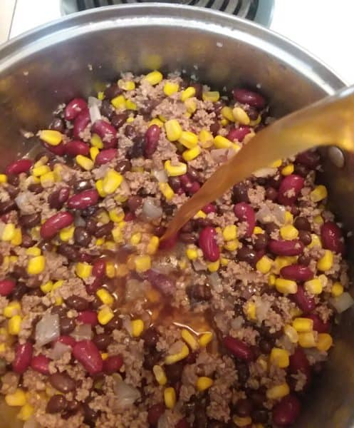 beef stock pouring into pot, taco soup